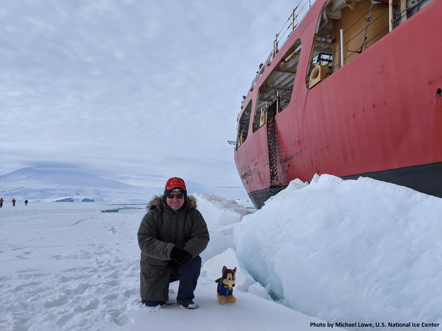 Senior Analyst Mike Lowe on the ice alongside USCGC Polar Star during Deep Freeze 2020